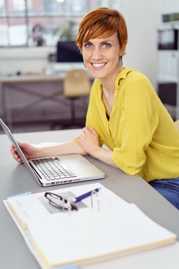 Single young happy red haired woman seated and leaning forward at gray desk with open laptop computer in office