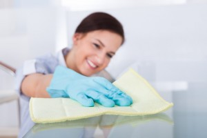 Smiling young maid cleaning glass table at home